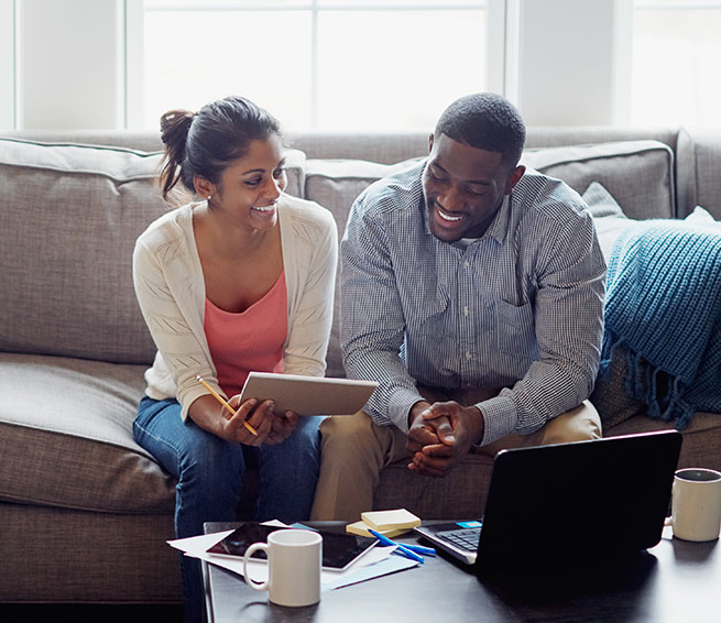 Man and woman sitting on couch in front of laptop